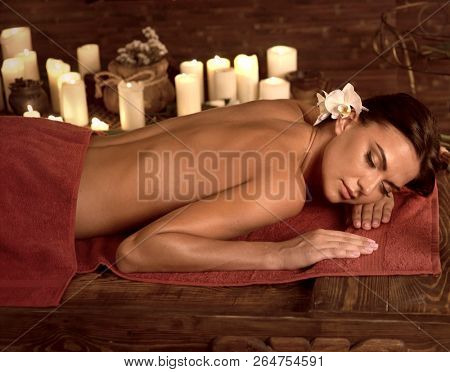 poster of Chiropractic ayurveda massage therapy of woman in spa salon. Girl on candles background in massage s