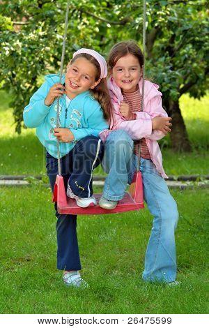 Twee jonge meisjes op de tuin schommel