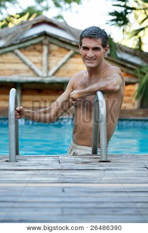 Portrait of handsome middle aged man standing in the swimming pool