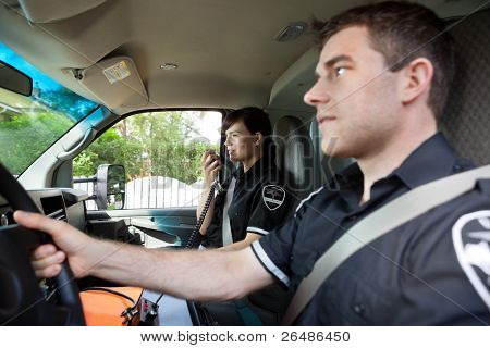 Paramedic talking on radio to dispatcher.  Shallow DOF critical focus on woman with handset
