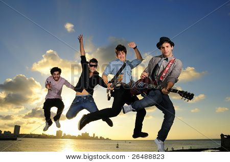 Band of young male musicians jumping with instruments against sunset sky background
