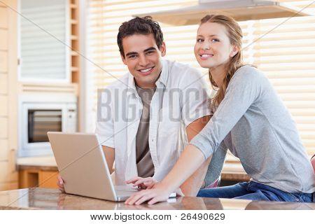 Pareja joven/esposos con el portátil en la cocina