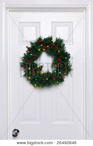 Photo of a Christmas wreath with lights hanging on a white front door.