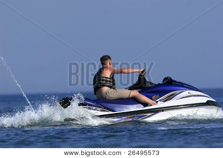 A man riding a blue white and yellow jet ski on the sea.