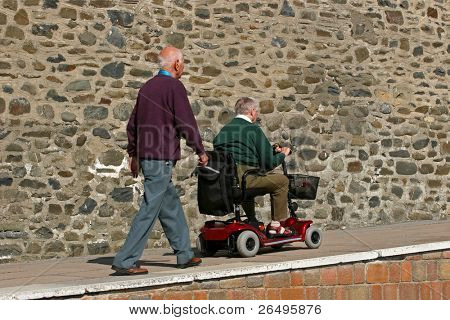 Disabled elderly man riding a mobility vehicle on an uphill path, with another elderly man walking behind.