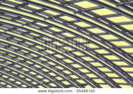 Abstract in shades of silver, yellow and black of the curved reinforced steel roof joists in a conservatory with glass panes in between.