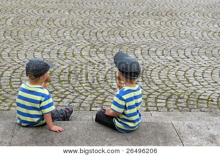 Two twin boys in matching clothes eating ice creams, sitting next to a cobblestone pavement.