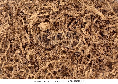 Concertina brown paper packaging filler forming an abstract textured background.