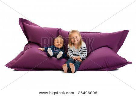 studio shot of two sister sitting on beanbag