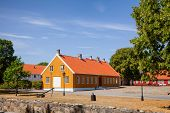 Ochre and red coloured historic buildings at Staverns Fortress (Fredriksvern), Larvik, Vestfold, Nor poster