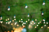 stock photo of christmas lights  - Hanging decorative christmas lights for a back yard party - JPG