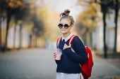 Pretty Hipster Teen With Red Bag Drinks Milkshake From A Plastic Cup Walking Street Between Building poster
