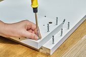 Joiner Is Screwing Locking Screws Of Flat Pack During Furniture Assembly. poster