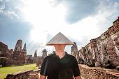 Portrait Of Man In Chinese Hat Standing Near The Ancient Ruins At Wat Mahathat In Ayutthaya Historic poster