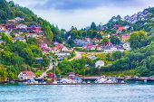 Norwegian Scandinavian Scenic Landscape With Fjord Water, Mountains And Colorful Traditional Village poster