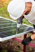 Close-up Of Professional Technician Working With Screwdriver Connecting Solar Photo Voltaic Panel To poster