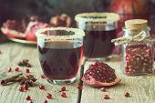 A Glasses Of Pomegranate Juice With Fresh Pomegranate Fruits On Wooden Table. Healthy Drink Concept. poster