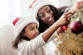 African American Mother And Daughter In Santa Claus Hats Decorating Christmass Tree Together At Home poster