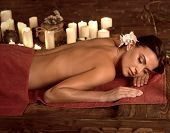 Chiropractic ayurveda massage therapy of woman in spa salon. Girl on candles background in massage s poster