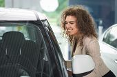 Pretty Woman Smiling And Looking At White Car. Female Client Of Car Center Smiling And Observing Aut poster