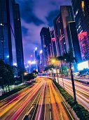 Street traffic in Hong Kong at night. Office skyscraper buildings and busy traffic on highway road w poster
