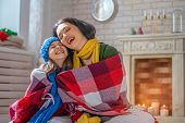 Winter portrait of happy loving family wearing knitted sweaters. Mother and child girl having fun, p poster