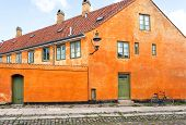 Street With Cobblestones And Cycle At Front Of Colorful House. Facade Of Historical Brick Building I poster