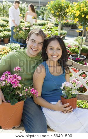 Portrait of a happy young couple with potted flower plants sitting on bench at botanical garden
