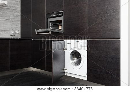 Build-in washing machine and cooker on modern black kitchen