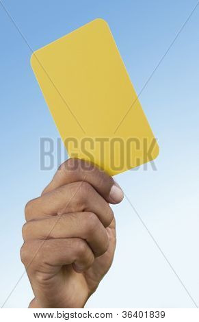 Close-up of referee's hand holding a yellow card that indicates a warning to a player for a foul