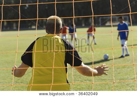 Rear view of soccer goalkeeper ready to save a shot from the opposite striker with teammates in the background
