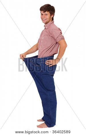 Young smiling healthy happy slim handsome guy in jeans, isolated on white