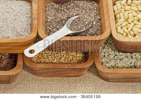 chia and other healthy seeds (gold and brown flax, hemp. pine nuts) in wooden bowl with measuring tea spoon