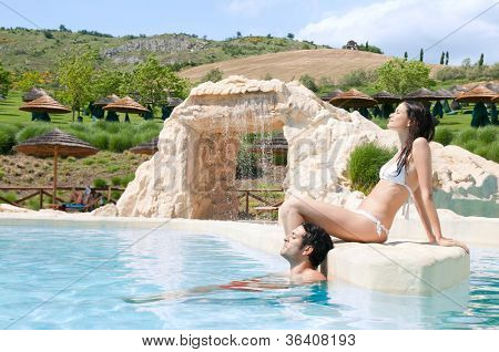 Beautiful young couple relaxing together in the swimmingpool of a resort