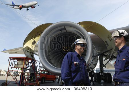 airplane mechanics with large jet engines in background, airliner coming in for landing