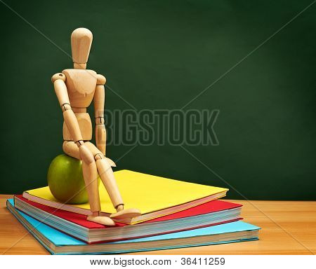 Back to School Series: wooden man sitting over stack of colorful books on the classroom desk with green board in the background
