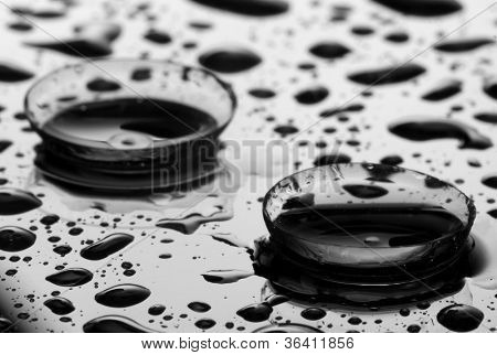 contact lens with drops on grey background