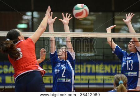 KAPOSVAR, HUNGARY - APRIL 22: Zsanett Pinter (blue 2) in action at the Hungarian I. League volleyball game Kaposvar (blue) vs Budai XI. SE (red), April 22, 2012  in Kaposvar, Hungary.