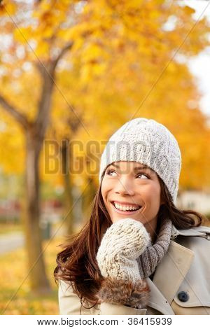 Fall woman thinking looking up in yellow autumn forest. Young happy smiling mixed race Caucasian and Chinese asian woman outdoors in city forest park.