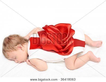 Sleeping newborn baby boy with red bow