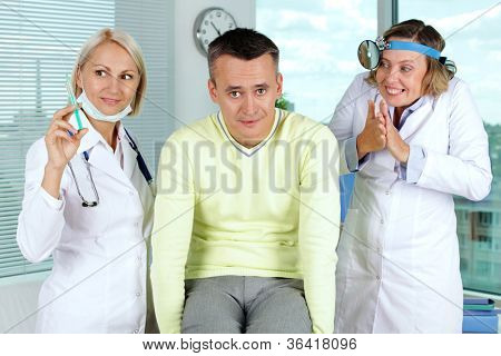 Portrait of two gloating female doctors giving first aid to male patient in hospital