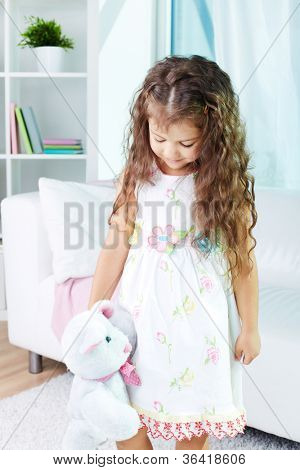 Portrait of lovely girl playing with teddybear in kindergarten