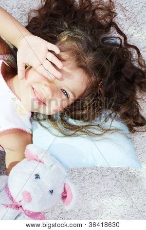 Portrait of lovely girl with teddybear rubbing her eyes after sleep