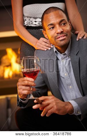 Goodlooking ethnic man sitting by fireplace smoking cigar, drinking wine, girlfriend standing behind.