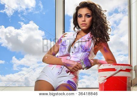 Smiling beautiful woman painting interior against window