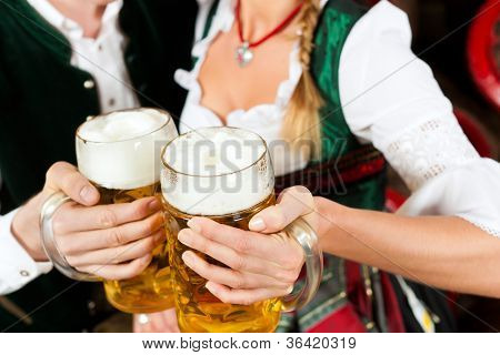 Young couple, man and woman, in traditional Bavarian Tracht drinking beer in a brewery in front of beer barrels