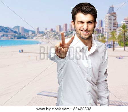 portrait of a handsome young man doing victory symbol against a beach