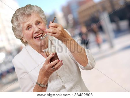portrait of senior woman eating chocolate and cream cup at street