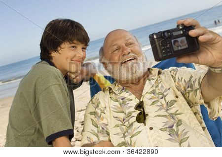 Senior man with grandson taking self-portrait through digital camera on beach