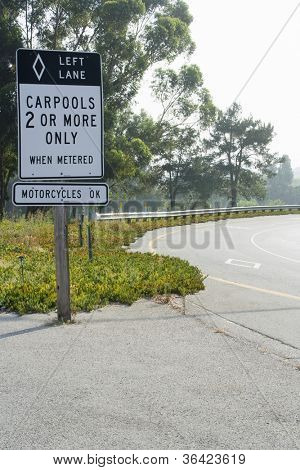 Overhead freeway carpool only sign on road